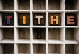 """The word """"TITHE"""" written in vintage ink stained wooden letterpress type in a partitioned printer's drawer."""